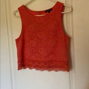 Salmon colored crop top with lace on the front